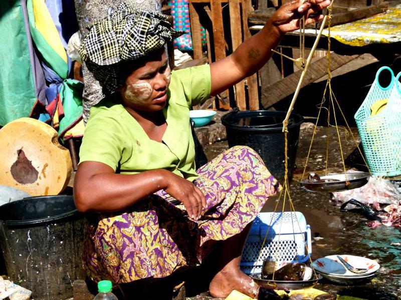 woman weighing fresh fish at a Yangon market
