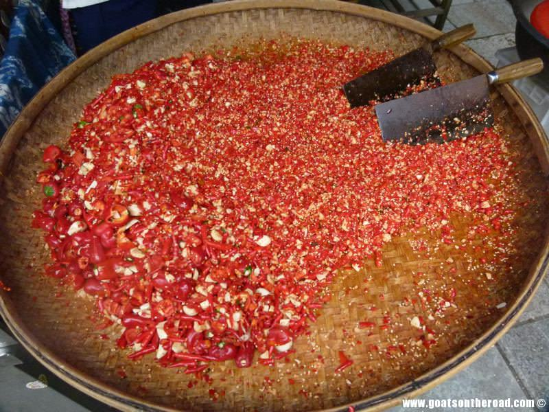 Fresh, red hot chilis being chopped up, Guilin, China