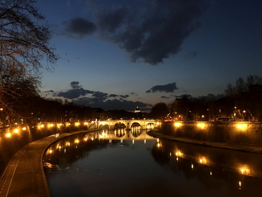 walking across the river at night in rome