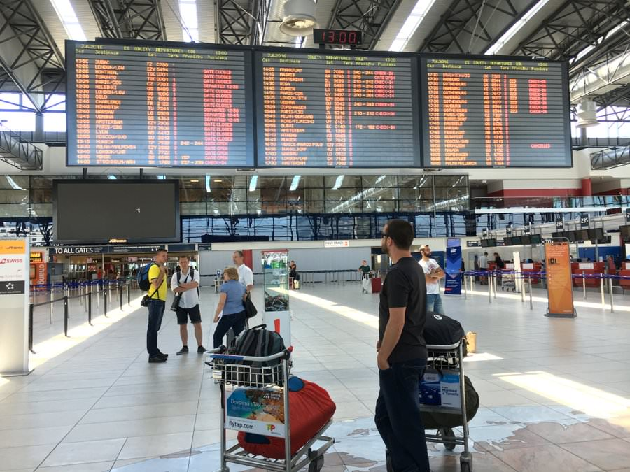 travel planning looking at departure board prague airport