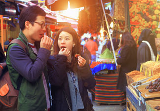 young-couple-trying-food-at-city-market