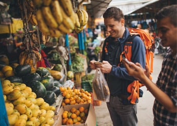 man buying fruit from local market abroad