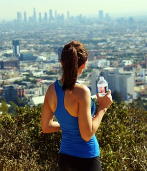 woman drinking bottled water overlooking los angeles