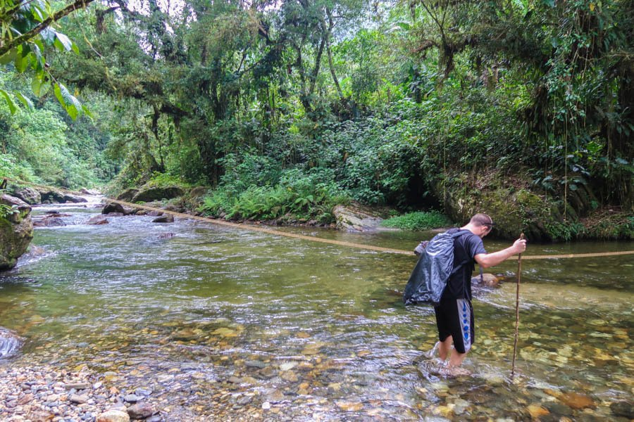 hiking the lost city in colombia river crossing