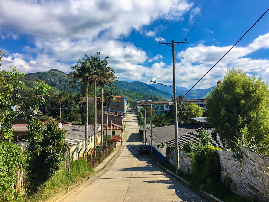 one of the main streets in the town of Salento, surrounded by mountains. This is one of the top backpacking spots in Colombia