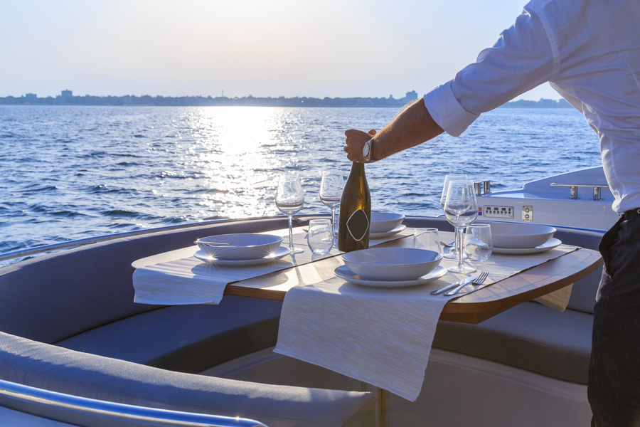 serving passengers wine while working on a yacht