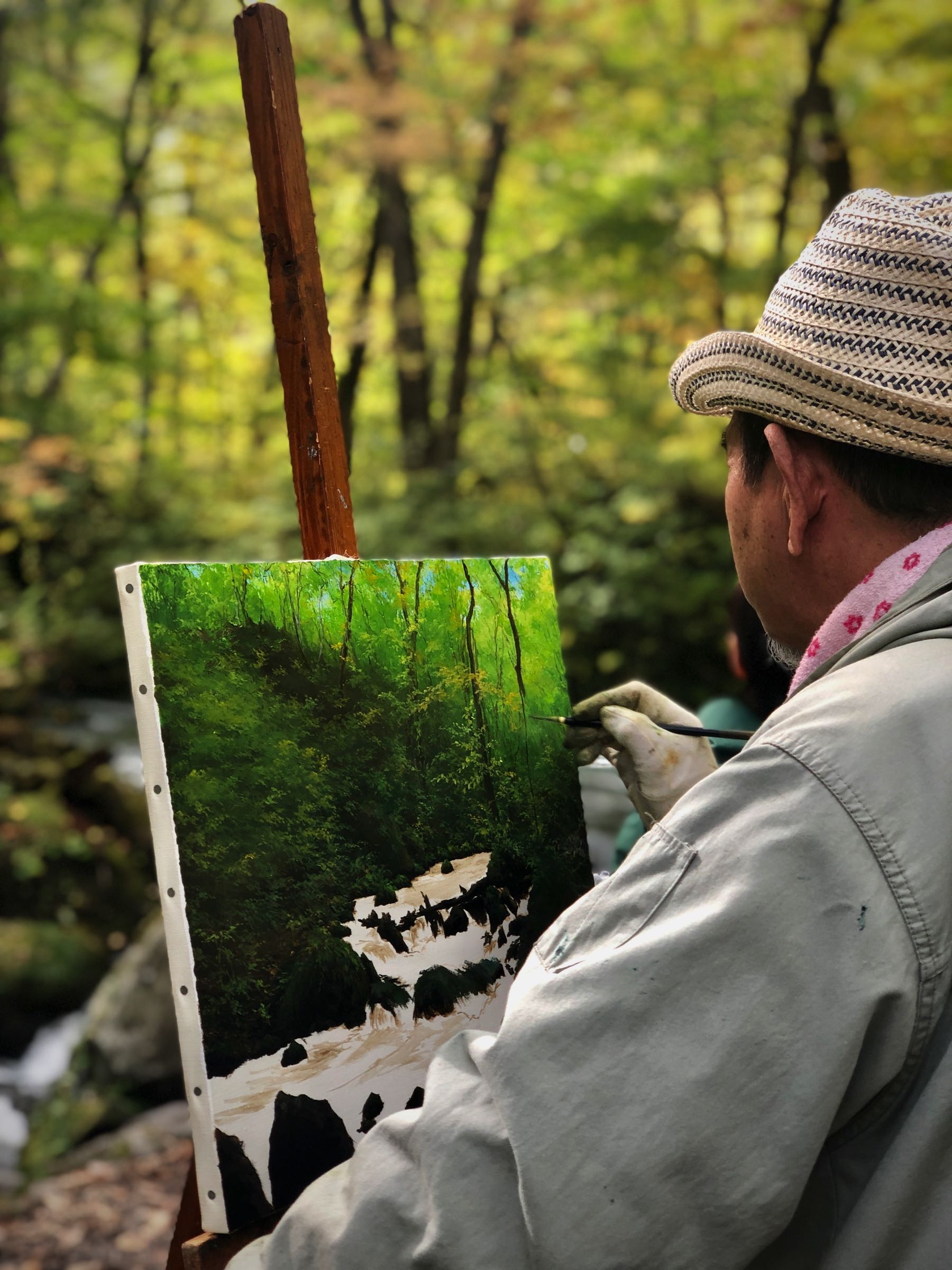 Man painting a scene in Oirase